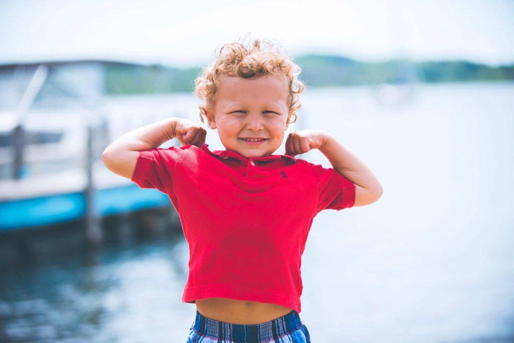 Healthy little boy flexing muscles